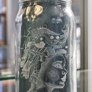 Lasimalja, johon on kaiverrettu koristeellinen naisen sivuprofiili