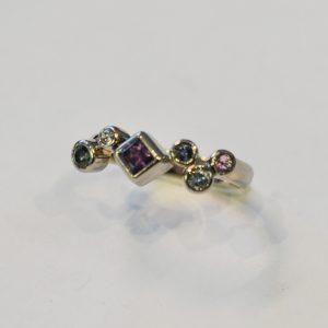 Lähikuva sormuksesta, jossa on monissa väreissä erikokoisia ja muotoisia kiviä