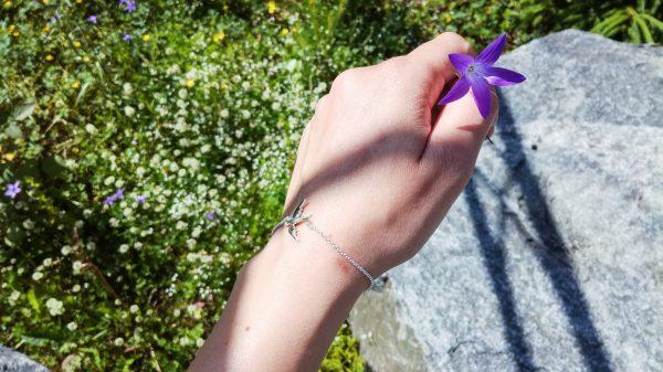 Käsi kukkakedon yllä ja kädessä variksenkello. Ranteessa hopeinen lintu rannekoru