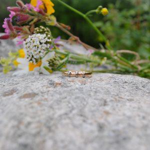 Kiven päällä on niittykukkia sekä keltakultainen sormus jossa on valkokultaiset oristeosat