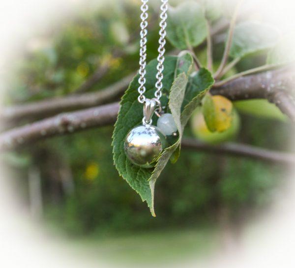 Omenapuunlehdellä hopeinen palloriipus sekä pieni riipus vaaleansiniselä kivihelmellä