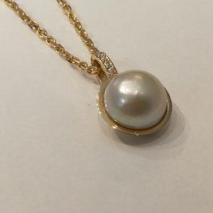 Keltakultainen riipus isolla valkealla helmellä sekä pienin timantein