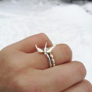 Sormessa hopeiset kapeat sormukset. Toisessa isompi lintukoruosa.