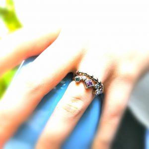 Lähikuva kädestä, jossa on kaksi valkokultaista sormusta toisessa on monenvärisiä kiviä
